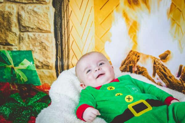 Baby smiling while wearing the Christmas Elf all-in-one